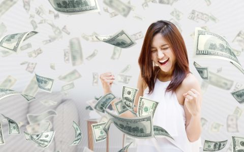 Young woman celebrating in a shower of money.